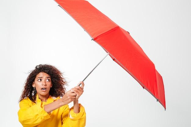 Beeld van verwarde afrikaanse vrouw die in regenjas haar paraplu over wit houdt