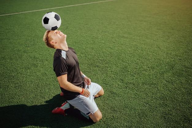 Beeld van voetbalsterzitting op knieën op gazon en greepbal op voorhoofd. hij kijkt op. guy beweegt niet. hij is geconcentreerd. het is zonnig buiten.