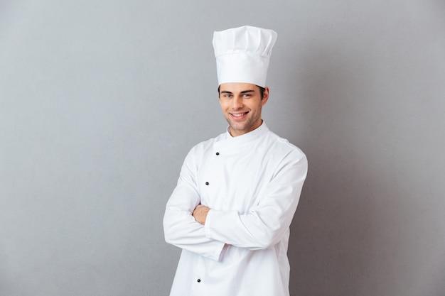 Beeld van vrolijke jonge kok in eenvormige status geïsoleerd over grijze muur