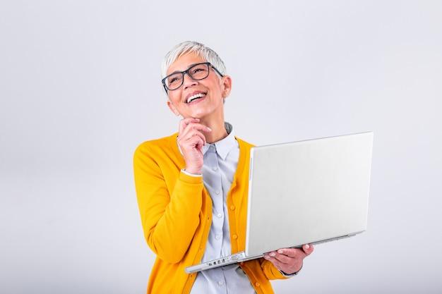 Beeld van vrolijke rijpe vrouw status geïsoleerd over grijze achtergrond die laptop computer met behulp van. portret van een glimlachende hogere laptop van de dameholding computer