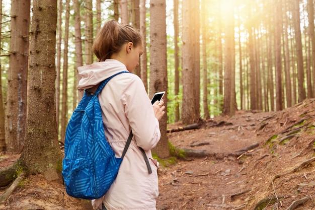 Beeld van vrouw die backpacker haar weg proberen te vinden, gebruikend mobiele telefoon in bos, wijfje die voor gang in lentetijd gaan