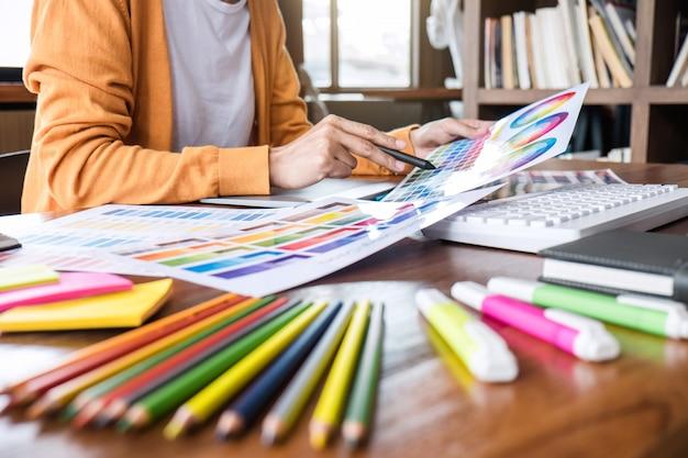 Beeld van vrouwelijke creatieve grafische ontwerper die aan kleurselectie werken en op grafiektablet trekken op het werk met het werkhulpmiddelen en toebehoren
