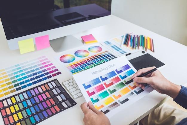 Beeld van vrouwelijke creatieve grafische ontwerper die aan kleurselectie werken en op grafiektablet trekken