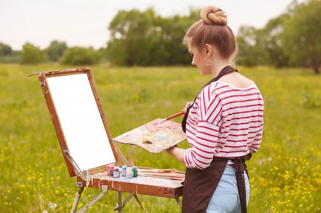 Beeld van vrouwelijke kunstenaar die met waterverf het schilderen werkt