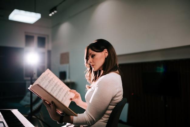 Beeld van vrouwelijke pianistzitting voor een bladmuziek van de synthesizerholding.