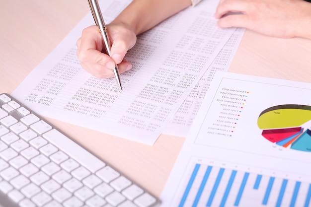 Beeld van vrouwenhand die op papier met aantallen schrijft