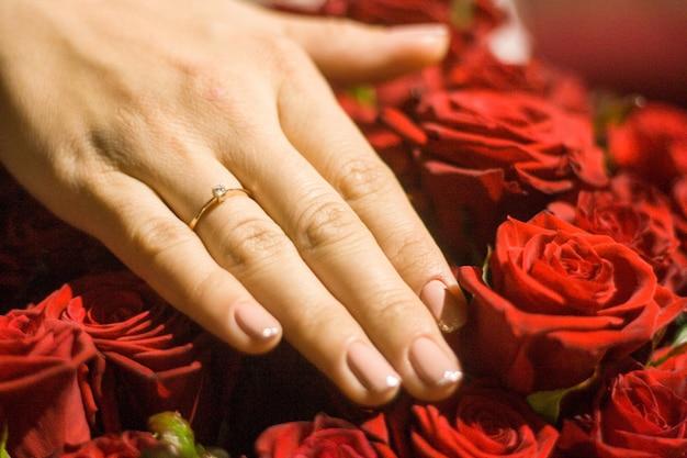 Beeld van vrouwenhand met trouwring op rozen