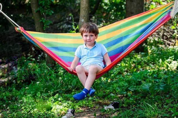 Beeld van weinig jongensplaatsing in hangmat openlucht.