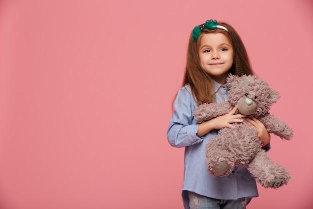 Beeld van zoet schoolmeisje met lang kastanjebruin haar dat houdend haar mooie teddybeer glimlacht