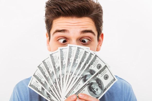 Beeldclose-up van de vermakelijke mens met donker kort haar die pret hebben en ventilator van geld in dollarbiljetten houden aan zijn gezicht, dat over witte muur wordt geïsoleerd