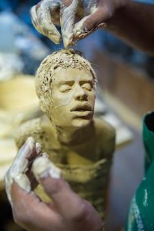 Beeldhouwer die het menselijk lichaam model maakt met klei
