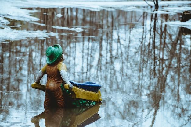 Beeldje in de vorm van kabouter staat met zijn rug met kruiwagen in water in het voorjaar