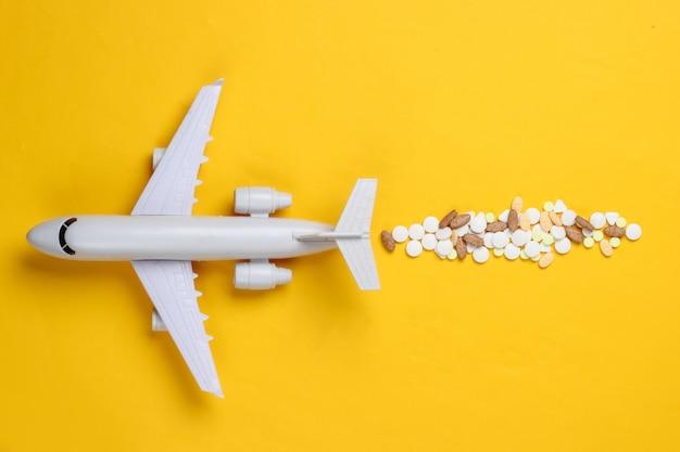 Beeldje van een passagiersvliegtuig met pillen op geel.