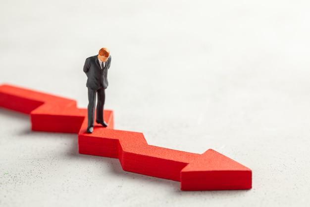 Beeldje van een zakenman in een pak en stropdas en een rode pijl naar beneden het concept van faillissement vallen