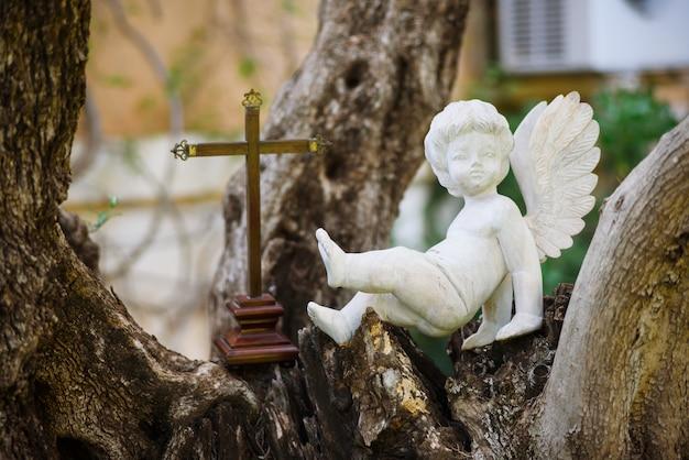 Beeldje van engel en een kruis op een boom buitenshuis.