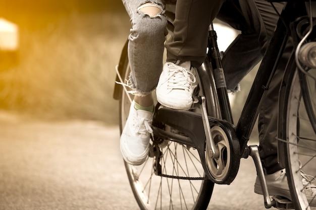 Been en voeten van jong paar die een fiets samen berijden