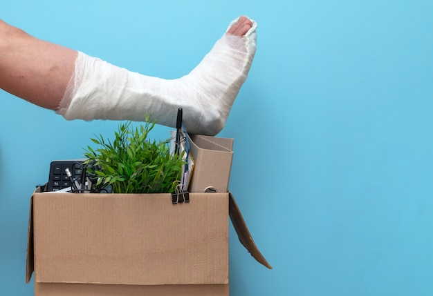 Been in gips over een doos van een ontslagen man van het werk op een blauwe achtergrond