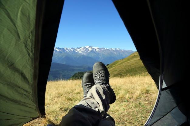 Been toerist in laarzen uit de tent met bergen in de