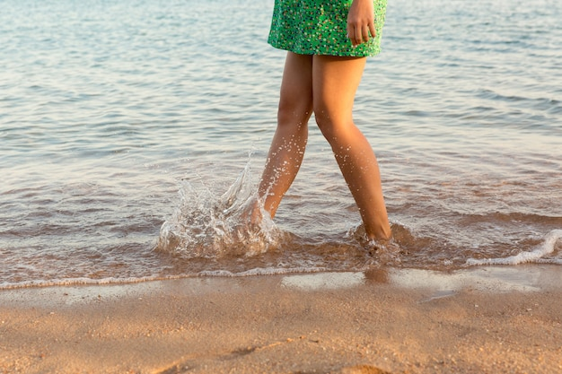 Been van vrouw die op strand met waterspatten loopt. zomervakantie. benen van een meisje die in water op zonsondergang lopen