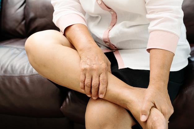 Beenkramp, hogere vrouw die aan beenkramppijn thuis lijden, gezondheidsprobleemconcept
