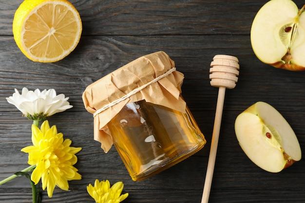 Beer, appel, citroen, bloemen en pot met honing op houten achtergrond