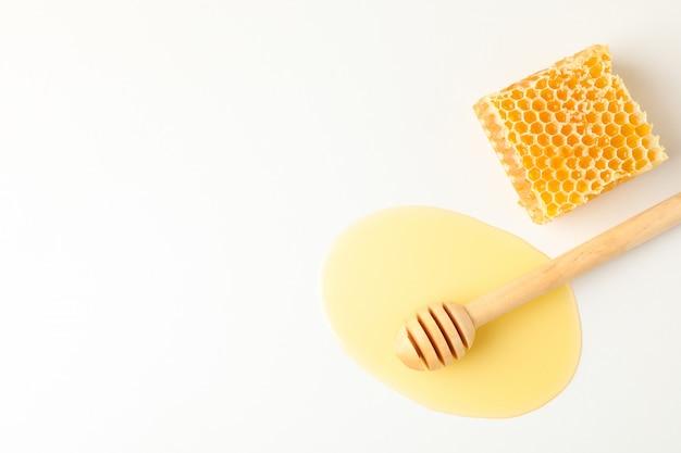 Beer in plas van honing en honingraat op witte achtergrond
