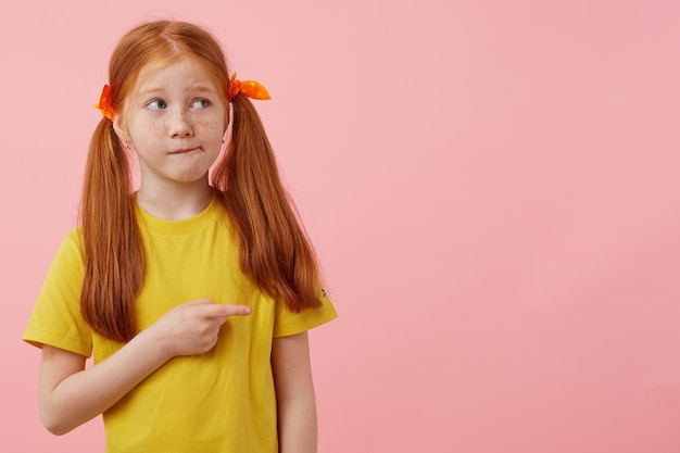 Beetje denkende sproeten roodharig meisje met twee staarten, kijkt weg, trekt je gewoon aandacht naar de kopieerruimte en wijzende vinger naar de rechterkant, staat op een roze achtergrond met kopieerruimte.