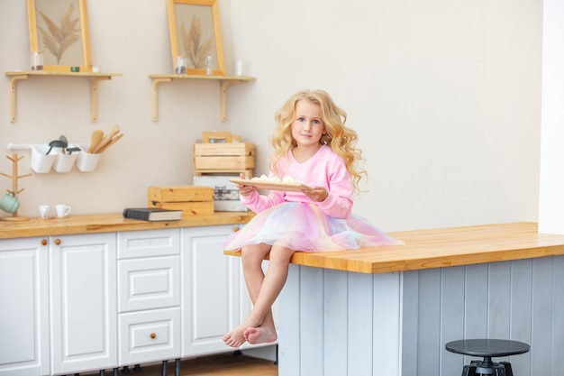 Beetje mooi kind meisje in de keuken thuis gelukkig en grappig