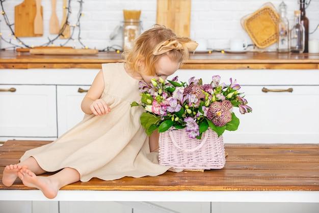 Beetje mooi kind meisje met bloemen in de keuken thuis