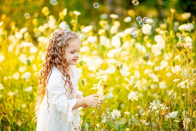 Beetje mooi meisje spelen op het gazon in de zomer met zeepbellen