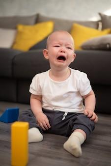 Beetje ongelukkig kind huilen op de vloer in zijn kamer