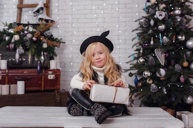 Beetje stijlvolle meisje poseren in de buurt van de boom van het nieuwe jaar in afwachting van kerstmis.
