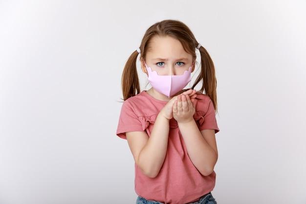 Beetje verdrietig meisje een rosa materiaal masker tegen virussen en bacteriën
