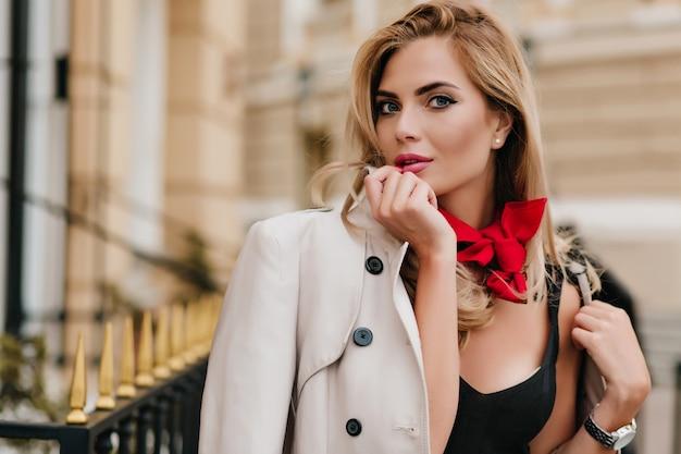Beetje verrast vrouwelijk model in jas poseren naast huis in de ochtend