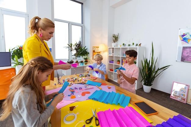 Begeleiden van leerlingen. leraar met blond haar in een gele jas die haar leerlingen helpt bij het maken van ornamenten