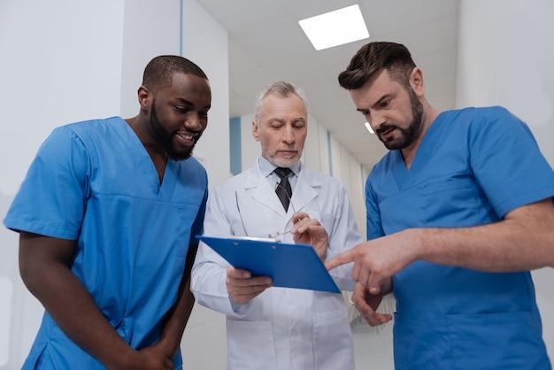 Begeleiden van mijn studenten. vriendelijke bekwame oudere professor die in het ziekenhuis staat terwijl hij de map vasthoudt en jonge artsen onderwijst