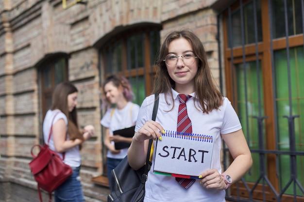 Begin. meisje student houdt notitieboekje met woord start, begin van de lessen op school, op de universiteit. bakstenen gebouw en pratende studenten achtergrond