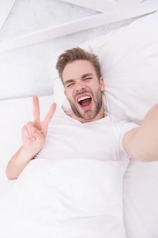 Begin van de goede dag. selfie tijd. gelukkige man maakt selfie op telefoon. goedemorgen. knappe man die selfie met mobiele telefoon neemt terwijl hij in bed ligt. man die een selfie maakt op bed. hallo.