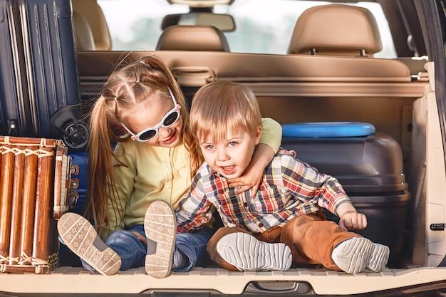 Begin van de reis kleine schattige kinderen in de kofferbak van een auto met koffers