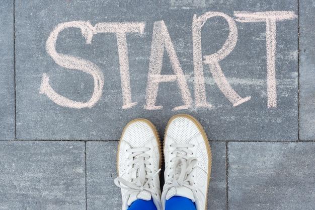 Beginconcept. tiener meisje staande benen op stoep voor woord handgeschreven krijt start. terug naar de universiteit