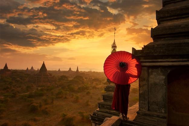 Beginnende monnik ontspannen in de oude tempel bagan tijdens zonsondergang, bagan, myanmar