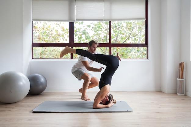 Beginnende yogi en zijn coach die yoga beoefent