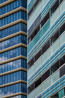 Beglaasde balkons en ramen van de gevels van twee stedelijke gebouwen in blauwachtige en groenachtige tinten