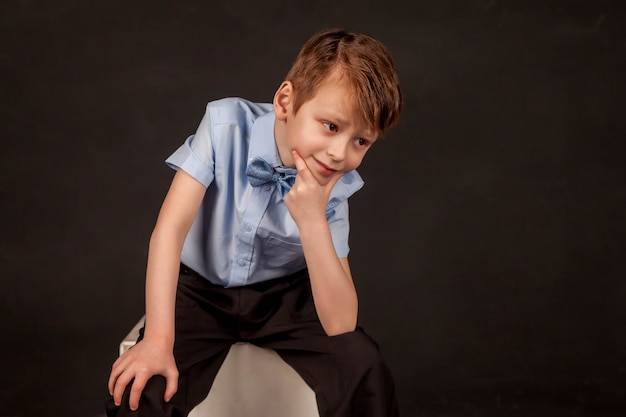 Begrip twijfel, alertheid en bedachtzaamheid - laat me nadenken. portret van een voorschoolse jongen met een verbaasde en serieuze uitdrukking op het gezicht, kind met de hand op de kin denkt, twijfelt, juiste keuze. ruimte kopiëren
