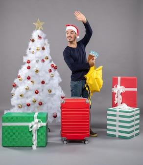 Begroetende jonge man met kerstmuts en rode koffer zijn gele rugzak rond verschillende cadeautjes controleren