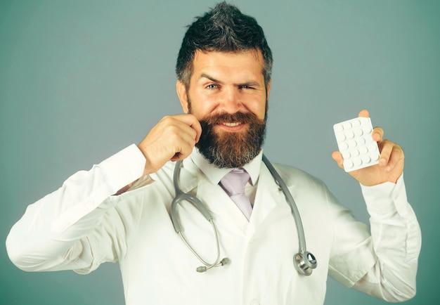 Behandeling en gezondheidszorg. glimlachende arts of verpleger met stethoscoop met pillen in de hand.