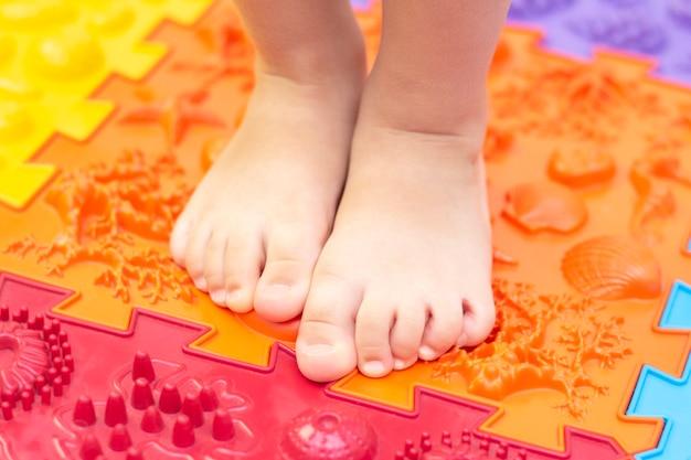 Behandeling en preventie van platvoeten bij kinderen. klein kind loopt blootsvoets op een orthopedische mat puzzel. gymnastiek voor voeten is nuttig voor het hele lichaam