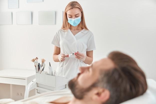 Behandeling van een jonge man door een schoonheidsspecialiste voor het aanhalen en gladstrijken van rimpels op de gezichtshuid. mesotherapie-injecties voor aantrekkelijke mannen.
