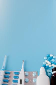 Behandeling van verkoudheid en griep. verschillende medicijnen, een thermometer, sprays van een verstopte neus en pijn in de keel op een blauwe achtergrond. kopieer ruimte. medicijn plat leggen