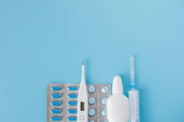 Behandeling van verkoudheid en griep. verschillende medicijnen, een thermometer, sprays van een verstopte neus en pijn in de keel op een blauwe. copyspace. medicijn plat leggen